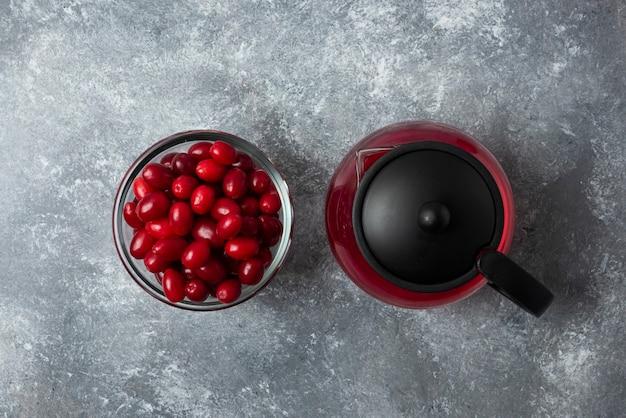 Cornels rouges dans une tasse en verre avec du jus dans la bouilloire.