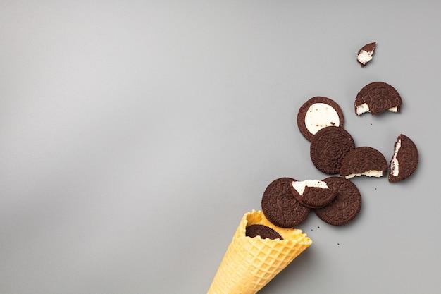 Cornet de crème glacée avec des biscuits aux pépites de chocolat avec garniture sur fond gris
