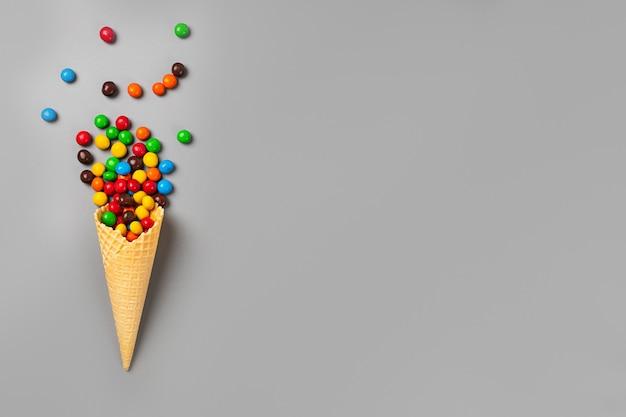 Cornet de crème glacée avec des bonbons multicolores sur fond gris