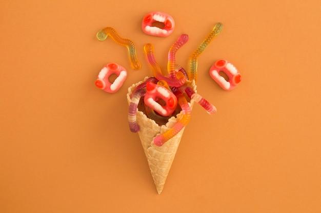 Cornet de crème glacée avec des bonbons pour halloween sur une surface orange. vue de dessus. espace de copie.