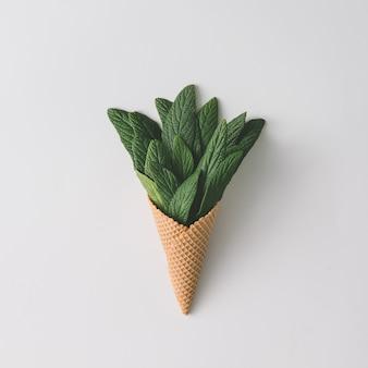 Cornet de crème glacée avec des feuilles vertes sur brillant