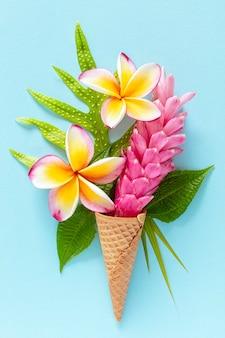 Cornet de crème glacée avec frangipanier fleurs tropicales et gingembre plume d'autruche sur fond bleu clair, mise à plat, composition verticale