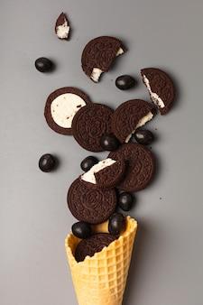 Cornet de crème glacée gaufre avec biscuits aux pépites de chocolat farcis de dragées au chocolat sur fond gris