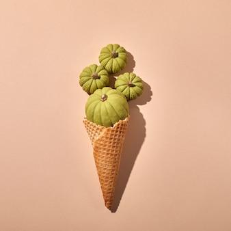 Cornet de crème glacée gaufre avec citrouilles vertes sur fond crème.