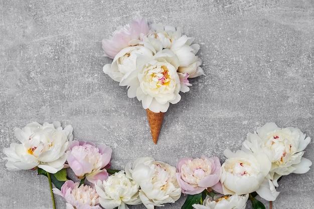 Cornet de crème glacée gaufre avec des fleurs de pivoine blanche sur fond gris. copier l'espace