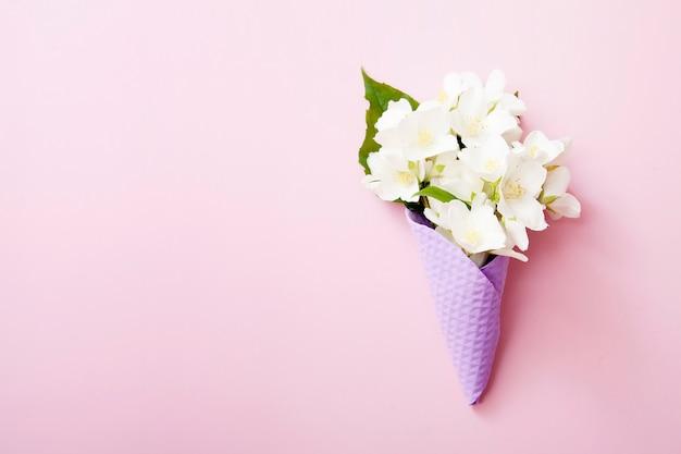 Cornet de crème glacée gaufre violet avec des fleurs de jasmin sur fond rose. concept d'été avec espace copie