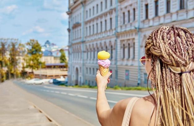 Cornet de crème glacée à la main en gros plan avec bokeh. gelato au sorbet pêche et saveur lavande.