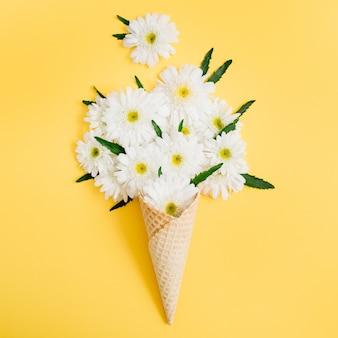 Cornet gaufré avec bouquet de fleurs de camomille sur jaune