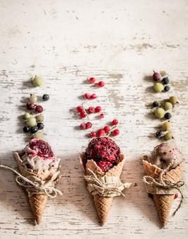 Cornet gaufré à la crème glacée aux fruits rouges sur fond de bois