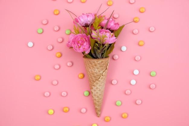 Cornet gaufré avec fleurs isolé sur rose