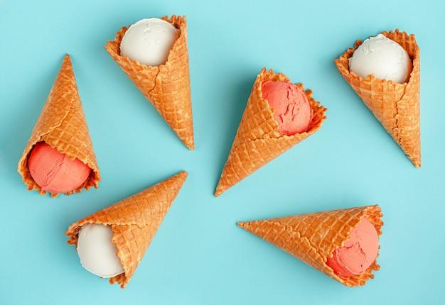 Cornets de crème glacée colorés sur fond bleu d'été, mise à plat.
