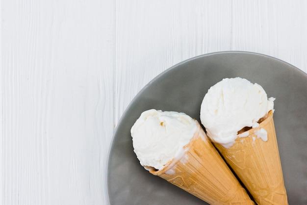 Cornets de crème glacée délicieux sur plaque sur une table en bois