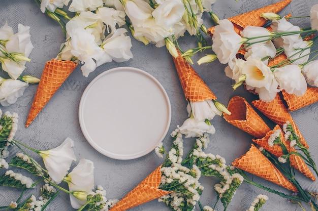 Cornets de crème glacée avec fleurs et assiette sur gris clair