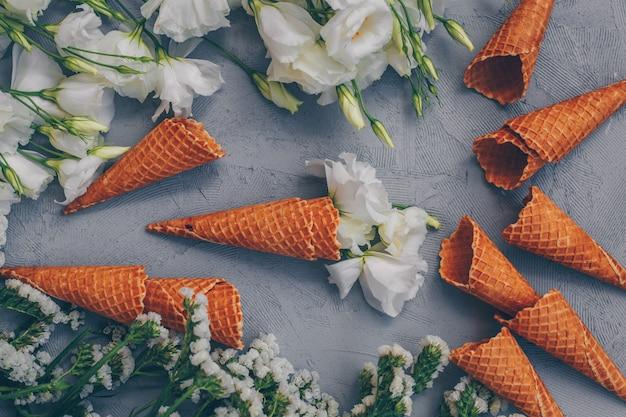 Cornets de crème glacée avec des fleurs vue de dessus sur blanc gris