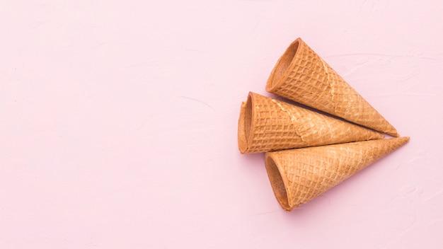 Cornets de crème glacée gaufres croustillants vides sur une surface rose