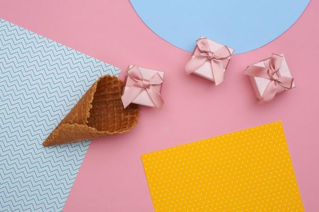 Cornets de gaufres à la crème glacée avec des coffrets cadeaux sur fond de papier coloré créatif, vue de dessus.