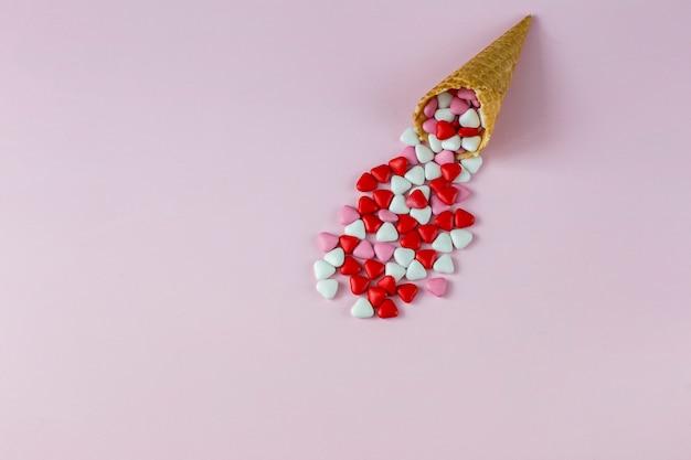 Cornets de glace sur fond rose et bonbons en forme de coeur