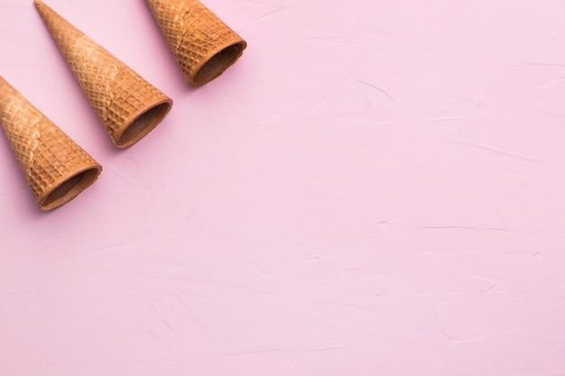 Cornets de glace vides marron sur fond rose