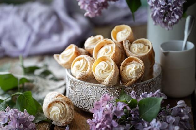 Cornets de pâte feuilletée à la crème à la vanille dans une boîte en métal au printemps nature morte avec un bouquet de lilas sur une table en bois