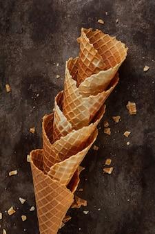 Cornets vides empilés faits maison ou cônes de gaufres de crème glacée sur fond sombre.