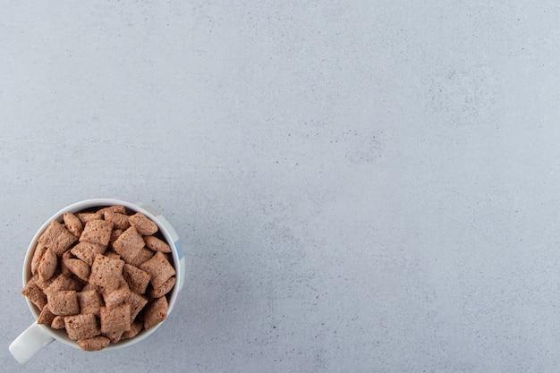 Cornflakes au chocolat dans une tasse en céramique sur fond de pierre. photo de haute qualité