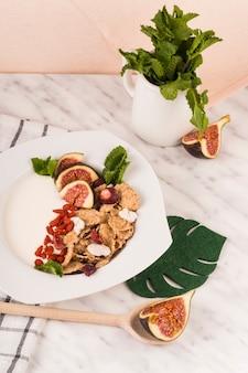 Cornflakes aux fruits de figue et feuilles de menthe sur une assiette décorée sur un plan de travail en marbre