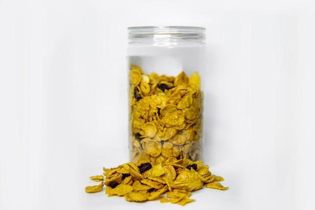Cornflakes aux noix de cajou, raisins secs et miel mélangés à une bouteille en plastique, isolés sur une surface blanche