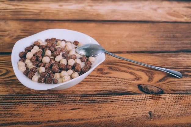 Cornflakes dans une assiette sur un bois.