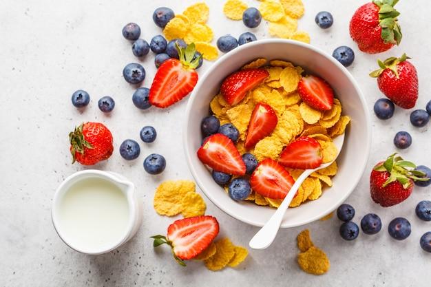 Cornflakes avec des fraises et des bleuets dans un bol sur fond blanc, vue de dessus.