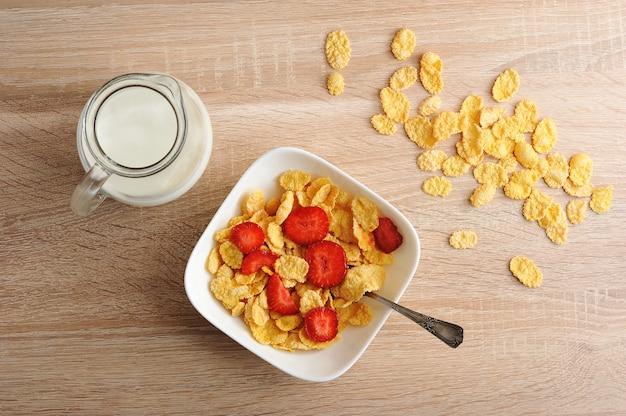 Cornflakes avec des fraises et un pot de lait sur une surface en bois