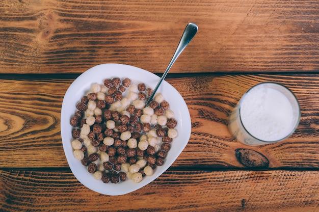 Cornflakes avec un verre de lait sur un bois.