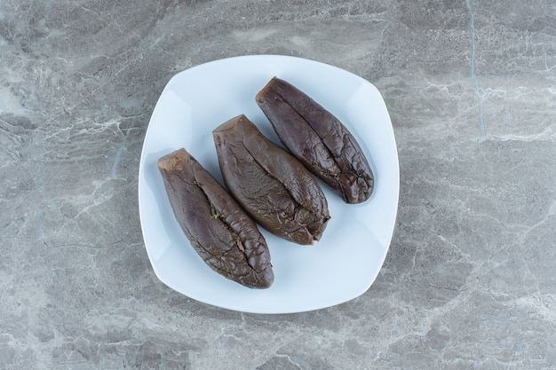 Cornichon frais fait maison. aubergine farcie sur plaque blanche. vue de dessus