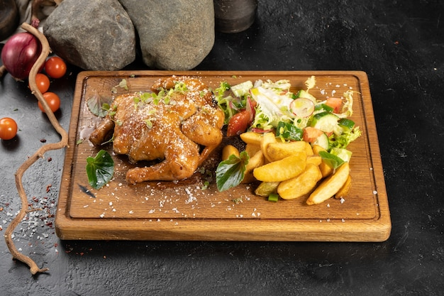 Cornichon de poulet au four avec pommes de terre et légumes frais sur une planche à découper en bois