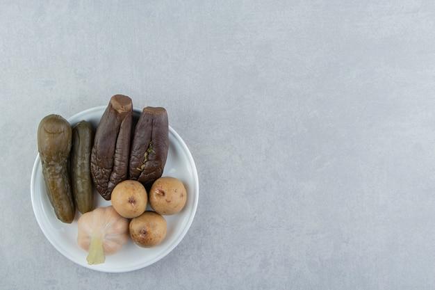 Cornichons assortis placés sur une assiette blanche.