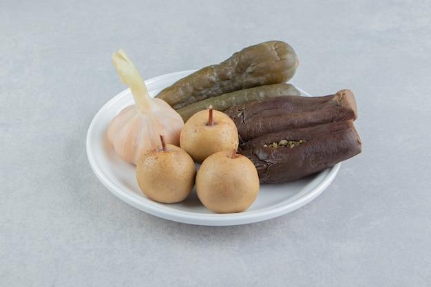 Cornichons assortis placés sur une assiette blanche