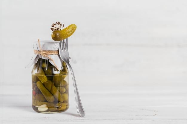 Cornichons, concombre mariné sur une fourchette, légumes marinés dans un bocal en verre sur une surface en bois blanche. manger propre, concept de nourriture végétarienne
