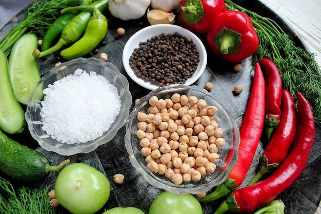 Cornichons sur table en bois blanc avec poivrons verts et rouges, fenouil, sel, grains de poivre noirs, ail, pois, gros plan, concept santé, vue de dessus, vue à plat