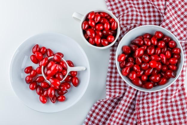 Cornouiller les baies dans différentes assiettes sur tissu blanc et pique-nique. pose à plat.
