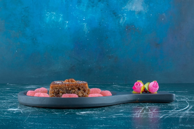 Corolles de fleurs à côté de marmelades autour d'une tranche de bakhlava sur un petit plat de service sur fond bleu. photo de haute qualité