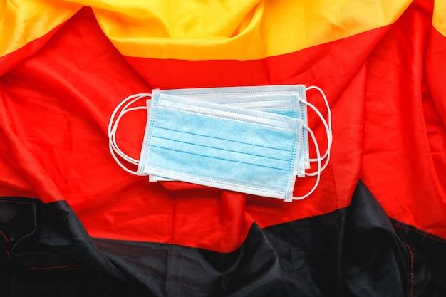 Coronavirus en allemagne. masque chirurgical protecteur sur le drapeau national deutsch. allemagne quarantaine, symbole de protection contre les coronavirus du médecin, infirmière, travailleur médical. soins de santé de médecine. covid-19