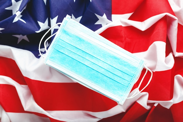 Coronavirus aux états-unis. masque protecteur chirurgical sur le drapeau national américain. drapeau américain et masque hygiénique comme symbole de protection contre la prévention des infections virales coronavirus, covid-19. médecine soins de santé