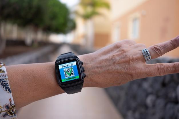 Coronavirus. bras de femme portant une montre électronique montrant le passeport numérique de la vaccination contre le coronavirus effectuée. application mobile pour les personnes immunisées