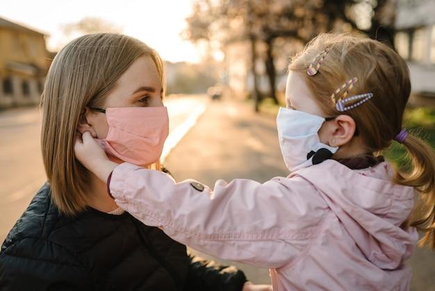 Coronavirus le concept de fin. plus de covid-19. petite fille, la mère porte des masques marche dans la rue. maman enlève le masque enfant heureux. famille avec enfant à l'extérieur. célébrer le succès. la pandémie est terminée, a pris fin.