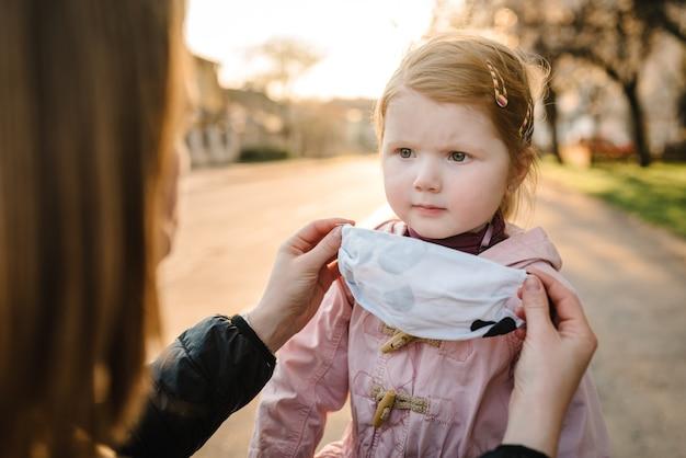 Coronavirus et concept de pollution de l'air. petite fille et mère portant des masques marchent dans la rue. maman corrige l'enfant masque. symptômes du virus pandémique. famille avec enfant à l'extérieur. protection contre les maladies.