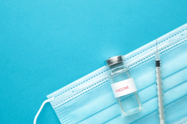 Coronavirus ou covid-19, 2019 - vaccin ncov dans une bouteille avec seringue et masque protecteur d'hygiène sur fond bleu. vue de dessus
