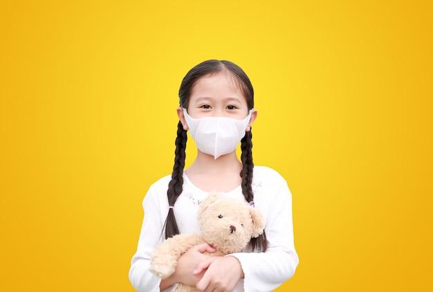 Coronavirus covid-19 et concept de protection contre la pollution. petite fille asiatique enfant étreignant poupée ours en peluche avec masque portant contre le virus corona et la pollution de l'air pm2.5 isolé sur fond jaune.