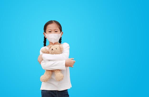 Coronavirus covid-19 et concept de protection contre la pollution. petite fille asiatique kid hugging nounours poupée avec masque portant contre le virus corona et la pollution de l'air pm2.5 isolé sur bleu avec copie espace