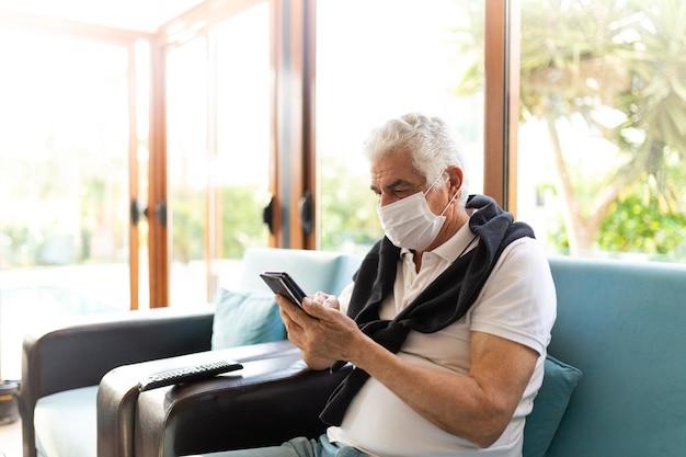 Coronavirus covid-19 homme âgé âgé à la maison s'asseoir sur le canapé dans un masque médical. surveiller son téléphone pendant la pandémie.restez à la maison