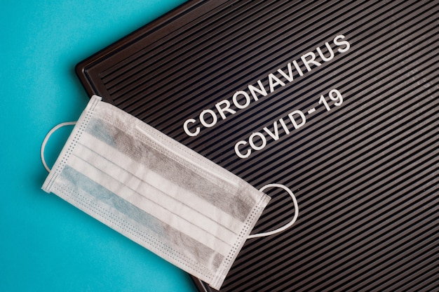 Coronavirus - covid -19 - texte sur lettre noire et masque chirurgical.