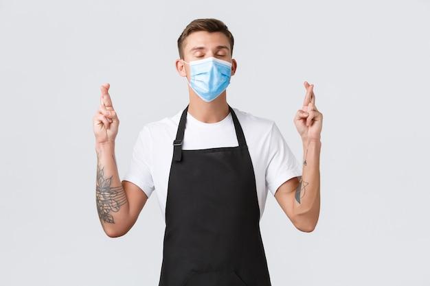 Coronavirus, distanciation sociale dans les cafés et restaurants, affaires pendant le concept de pandémie. barista optimiste plein d'espoir, employé dans un masque médical ferme les yeux et croise les doigts pour la bonne chance, faisant un vœu